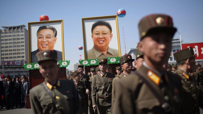 North Korean soldiers attend the opening of the Ryomyong residential area, while in the background, portraits of late North Korean leaders Kim Il Sung and Kim Jong Il are seen, on April 13, 2017, in Pyongyang, North Korea.