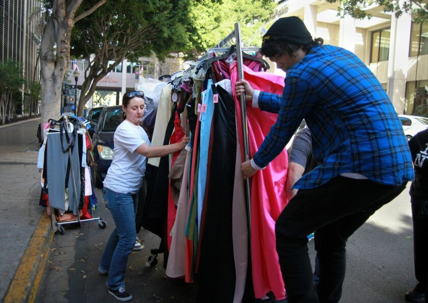 Jennifer Gaston, chairwoman of The Princess Project San Diego, and volunteer Oshea Piscopo of Chula Vista load a moving truck with prom dresses and other formal gowns to transport to an empty storefront inside Horton Plaza Saturday. Misael Virgen