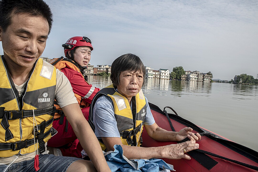 Zhang Meifeng and son-in-law Gao return to their flooded home on a rescue boat.