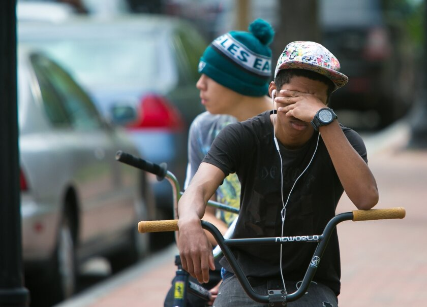 A student cries in front of Howard High School of Technology on Thursday, April 21, 2016 in Wilmington, Del.  A 16-year-old sophomore died Thursday following a fight in a Delaware high school girl's restroom, city officials said. (Suchat Pederson/The Wilmington News-Journal via AP)  NO SALES; MANDA