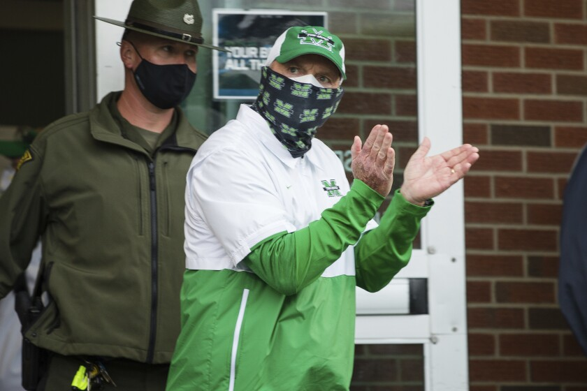 Marshall head coach Doc Holliday leads the players on to the field for a game against Florida Atlantic during an NCAA football game on Saturday, Oct. 24, 2020, at Joan C. Edwards Stadium Huntington, W.Va. (Sholten Singer/The Herald-Dispatch via AP)