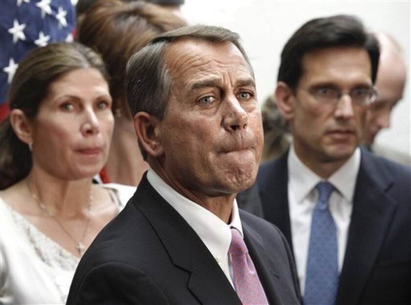 House Speaker John Boehner of Ohio, flanked by House Majority Leader Eric Cantor, R-Va., right, and Rep. Mary Bono Mack, R-Calif., pauses during a news conference on Capitol Hill in Washington, Friday, April 8, 2011. (AP Photo/J. Scott Applewhite)