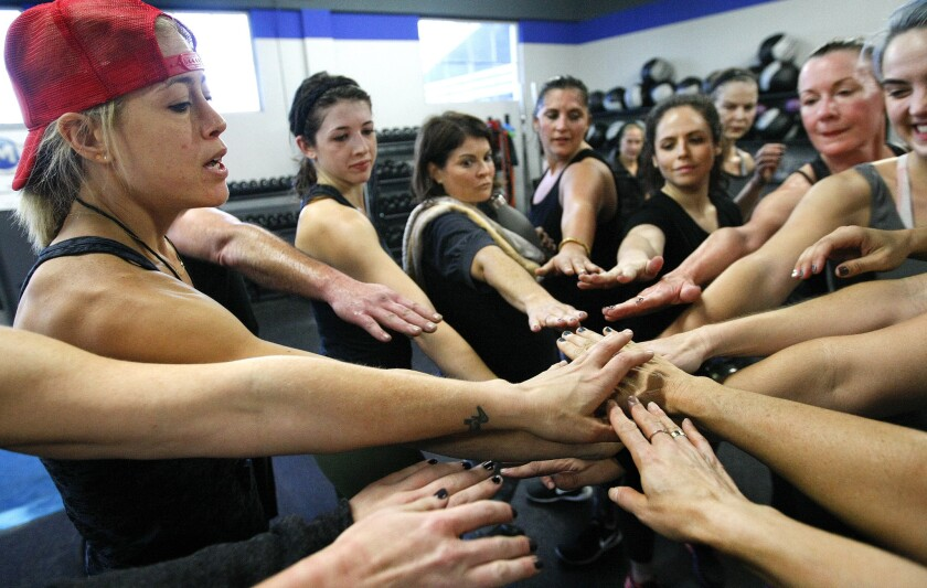 Fitness trainer Lacey Stone, left, joins hands with her students at the end