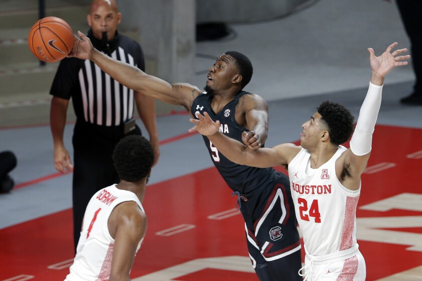 South Carolina guard Jermaine Couisnard (5) reaches for a ball over Houston guard Quentin Grimes (24) as forward Justin Gorham, left, looks on during the first half of an NCAA college basketball game Saturday, Dec. 5, 2020, in Houston. (AP Photo/Michael Wyke)