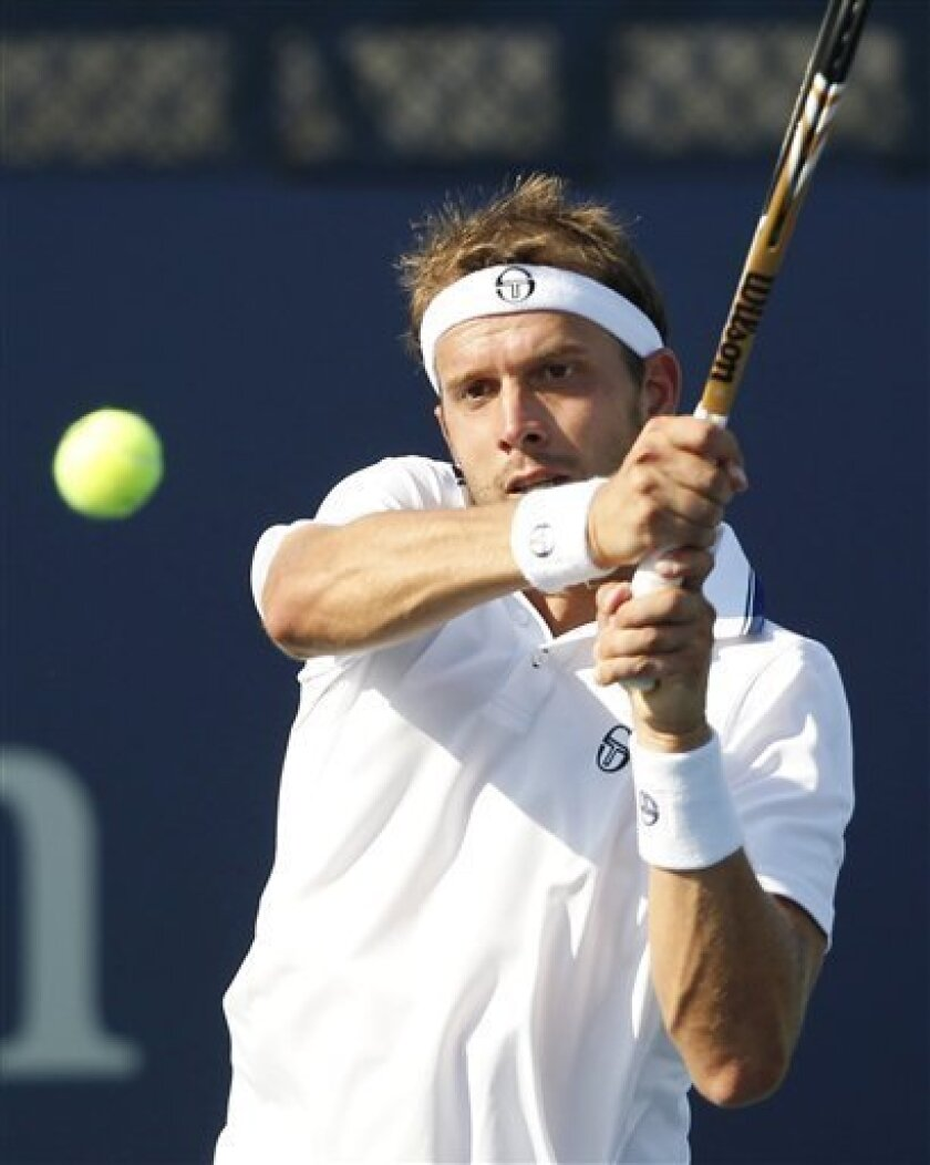 Gilles Muller, of Luxembourg, returns a shot to Australia's Lleyton Hewitt in the third round of play at the 2012 US Open tennis tournament,  Friday, Aug. 31, 2012, in New York. (AP Photo/Mel C. Evans)