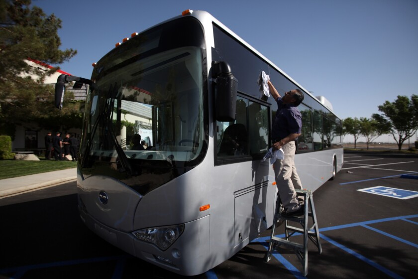 Joaquin Clara Lopez of Palmdale washes the windows of a new bus before a press conference where BYD and the city of Lancaster announced a new manufacturing facility in Lancaster.