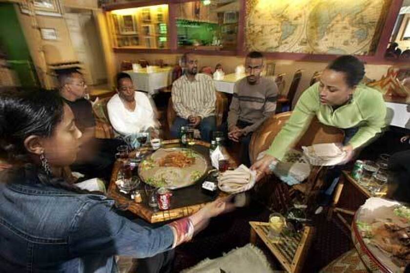 The family of Bernahu Asfaw gathers at his Messob restaurant in the neighborhood dubbed Little Ethiopia.