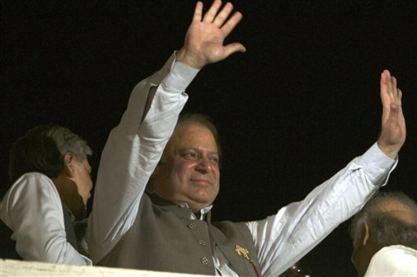 Former Prime Minister and leader of the Pakistan Muslim League-N party Nawaz Sharif waves to his supporters at a party office in Lahore, Pakistan, Saturday, May 11, 2013. Sharif declared victory following a historic election marred by violence Saturday, as unofficial, partial vote counts showed his party with an overwhelming lead. (AP Photo/K.M. Chaudary)