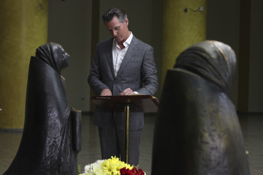 California Gov. Gavin Newsom writes a note on a book at the the tomb of Archbishop Oscar Romero at M