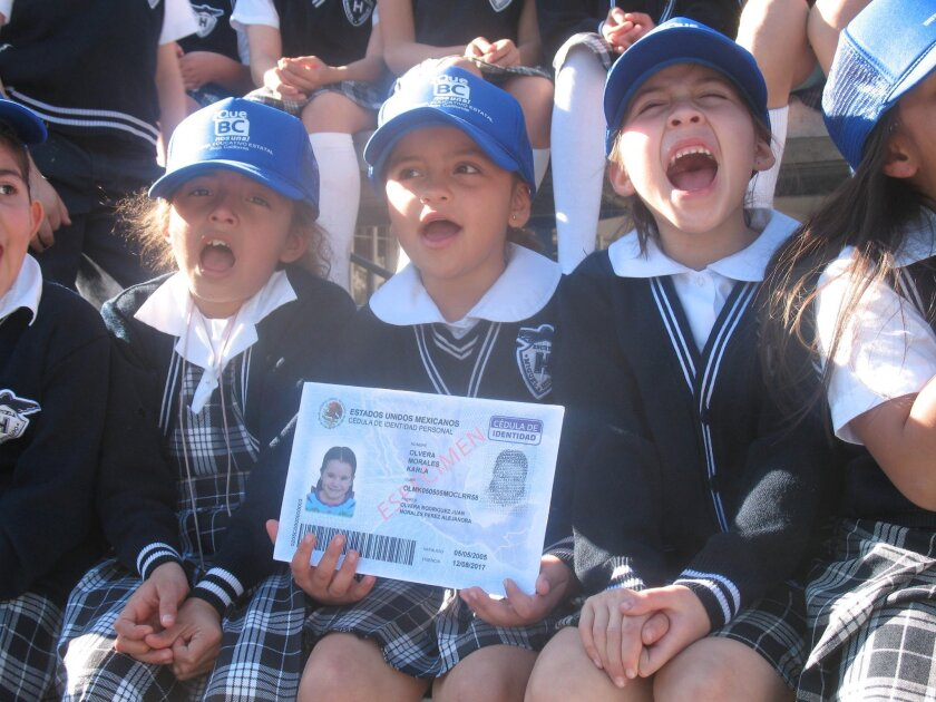 Kathy Fernandez Davalos (holding a giant version of the I.D. card) and her second-grade classmates at Miguel Hidalgo Elementary in Tijuana marked the launch of Mexico's new identification document program for minors Monday.