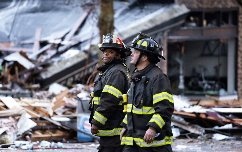 Firefighters stand near the smoldering rubble left from an early morning explosion Wednesday, March 9, 2016, in Seattle. The explosion heavily damaged buildings and injured multiple firefighters. (AP Photo/Elaine Thompson)