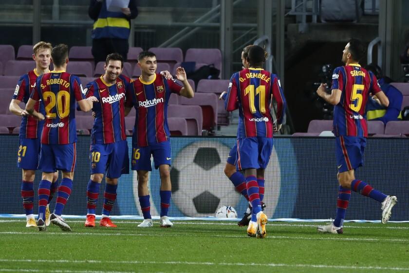 Lionel Messi (tercero a la derecha) tras marcar de penal el tercer gol del Barcelona