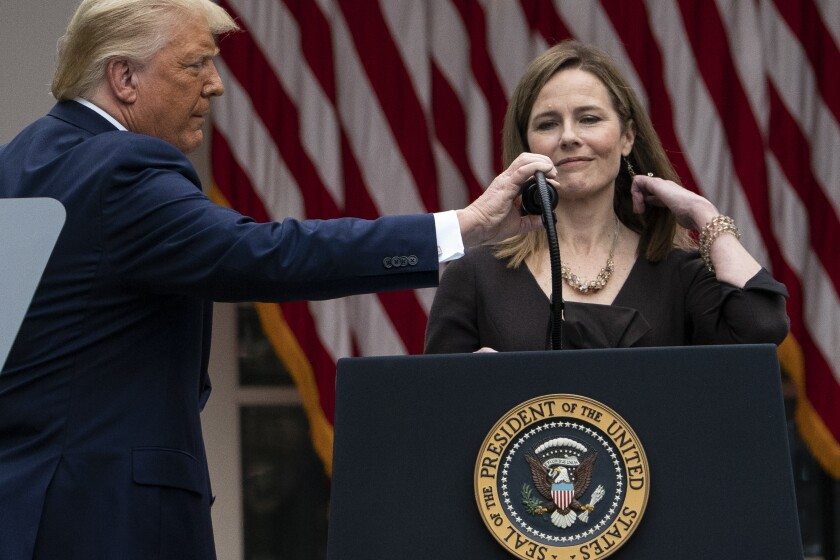 President Trump adjusts a microphone for Judge Amy Coney Barrett