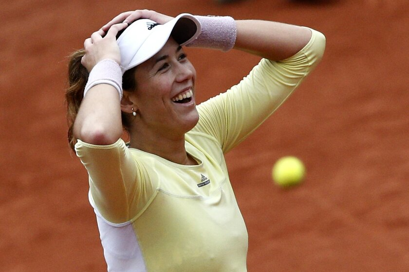 Spain's Garbine Muguruza smiles after defeating Australia's Samantha Stosur walk back after their semifinal match of the French Open tennis tournament at the Roland Garros stadium, Friday, June 3, 2016 in Paris. Muguruza won 6-2, 6-4. (AP Photo/Christophe Ena)