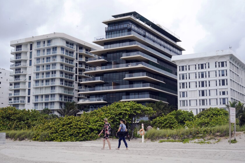 Beachgoers walk by the beach entrance to the Arte by Antonio Citterio condominium, center, Tuesday, June 29, 2021, in Surfside, Fla. Jared Kushner and Ivanka Trump rent an apartment at Arte while their home is under construction at nearby Indian Creek Village. (AP Photo/Marta Lavandier)