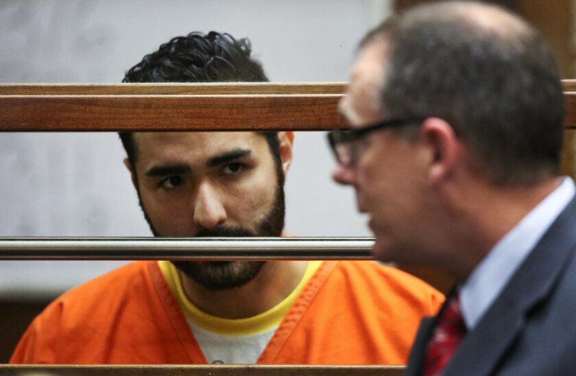 FILE - In this June 19, 2015, file photo, Henry Solis, a former Los Angeles police officer, left, appears with attorney Mearl Lottman at Los Angeles Superior courtroom in Los Angeles. Family members of Salome Rodriguez Jr., who prosecutors say was killed by Solis, an off-duty Los Angeles police roo