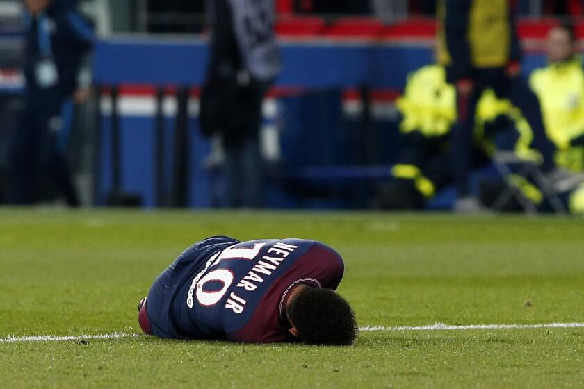 El jugador de PSG, Neymar, aparece tirado en el césped tras sufrir una lesión en un partido contra Marsella por la liga francesa el domingo, 25 de febrero de 2018, en París.