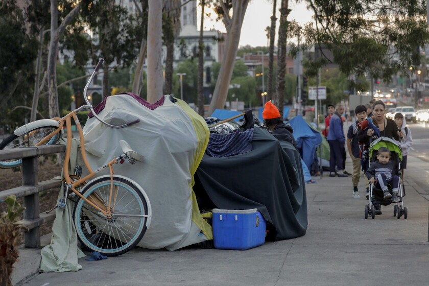 Pedestrians walk past tents along Arcadia Street in downtown Los Angeles in 2018.