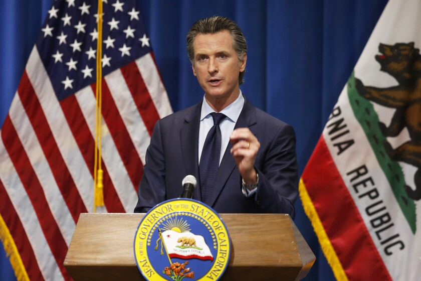 California Gov. Gavin Newsom is flanked by the U.S. and California flags during a news conference in May.