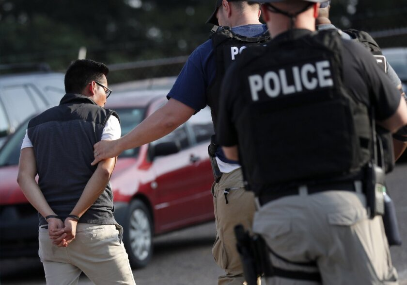 In this Aug. 7, 2019, file photo, a man is taken into custody at a Koch Foods Inc. plant in Morton, Miss. Unauthorized workers are jailed or deported, while the managers and business owners who profit from their labor often aren't. Under President Donald Trump, the numbers of owners and managers facing criminal charges for employing unauthorized workers have stayed almost the same. (