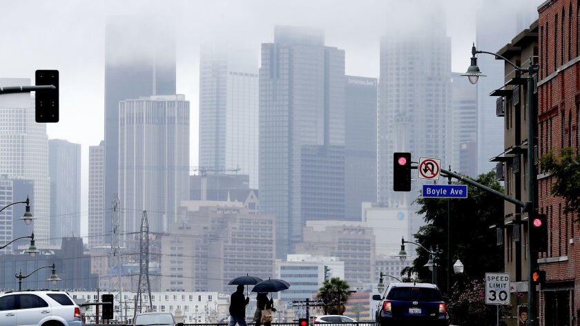 Pedestrians cross First Street in Boyle Heights as rain clouds partially obscure the downtown L.A. skyline on March 6.