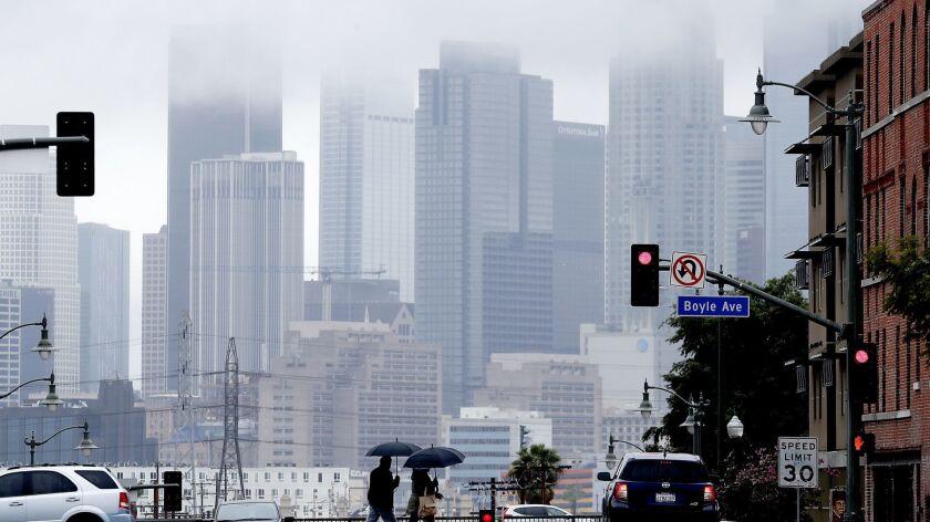 LOS ANGELES, CALIF. - MAR. 6, 2019. Pedestrians cross First Street in Boyle Heights as rain clouds p