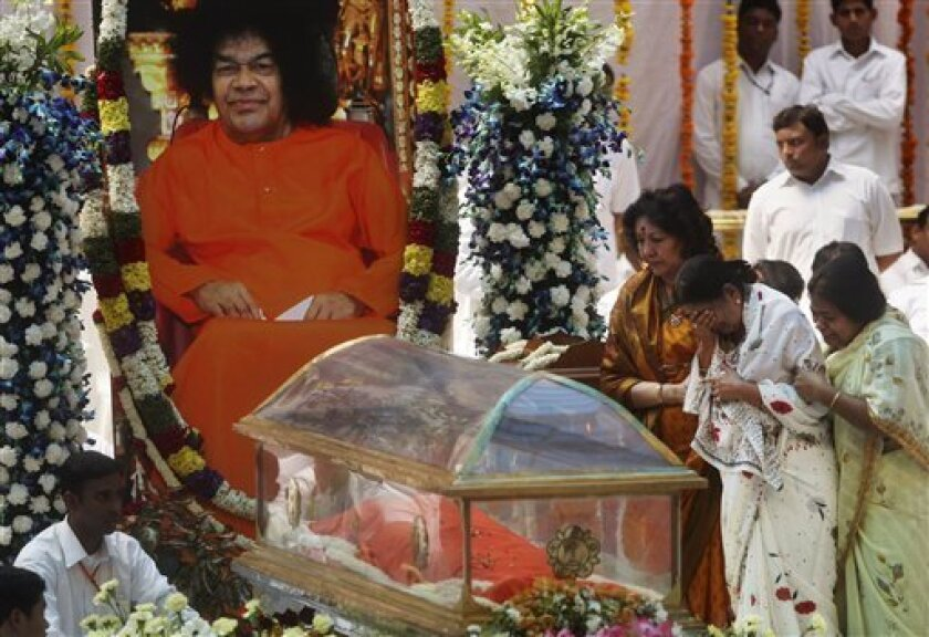 Devotees mourn near the body of Hindu holy man Sathya Sai Baba during a public viewing at the Prasanthi Nilayam Ashram in Puttaparti, India, Monday, April 25, 2011. Thousands of mourners on Monday paid their last respects to the Indian religious leader revered by millions for spiritual and healing powers but dismissed by some as a charlatan who passed off magic tricks as miracles. (AP Photo/Rafiq Maqbool)