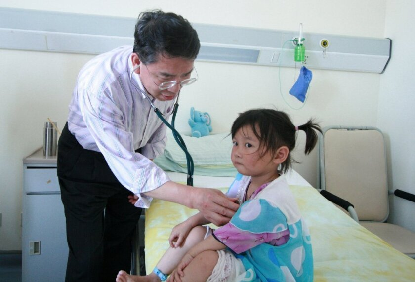 During a July 2015 visit to Zhangzhi city in the Shanxi province of China, Dr. William Wang examined a girl before her surgery for a congenital heart defect. / courtesy photo