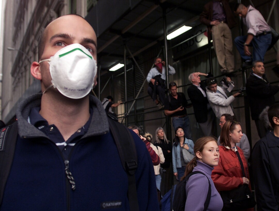 A man in a protective mask stands next to a group of onlookers
