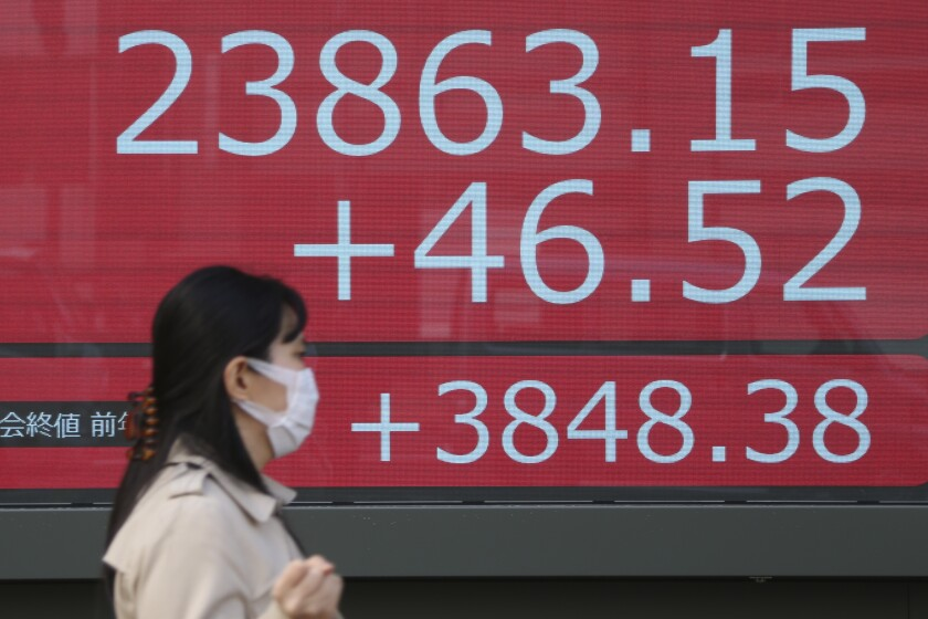 A woman walks by an electronic stock board of a securities firm in Tokyo, Monday, Dec. 23, 2019. Shares were mixed Monday in quiet trading ahead of Christmas holidays for many markets. (AP Photo/Koji Sasahara)