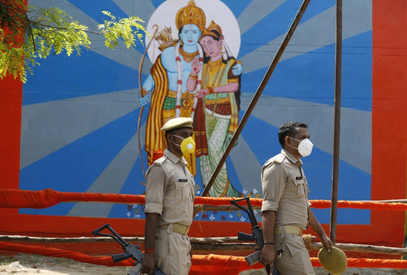 Policemen walk past an image of Hindu god Ram on the eve of a groundbreaking ceremony of a temple dedicated to Ram in Ayodhya, India, Tuesday, Aug. 4, 2020. Wednesday's groundbreaking ceremony follows a ruling by India's Supreme Court last November favoring the building of a Hindu temple on the disputed site in Uttar Pradesh state. Hindus believe their god Ram was born at the site and claim that the Muslim Emperor Babur built a mosque on top of a temple there. The 16th century Babri Masjid mosque was destroyed by Hindu hard-liners in December 1992, sparking massive Hindu-Muslim violence that left some 2,000 people dead. (AP Photo/Rajesh Kumar Singh)