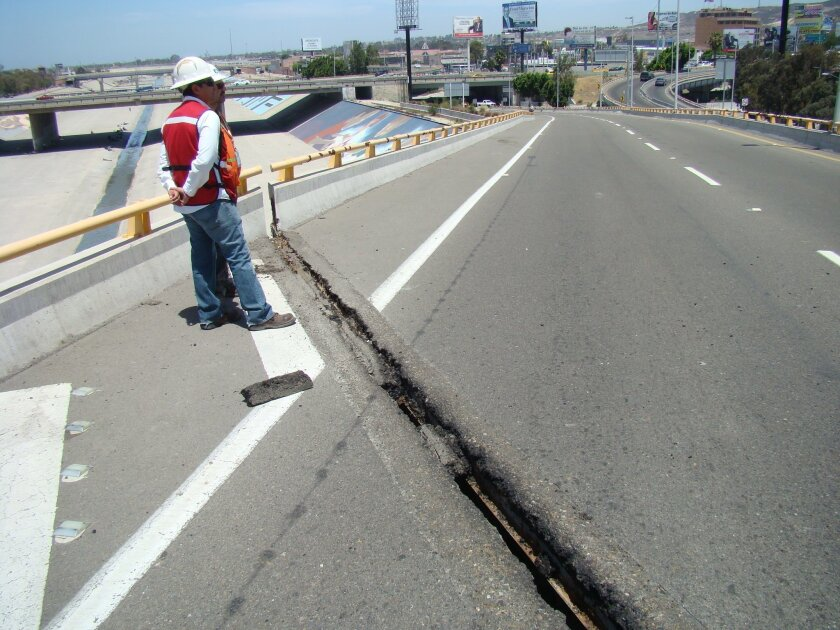 A worker on Wednesday stands near a damaged expansion joint on a bridge leading from Tijuana's El Chaparral port of entry to a major city highway.