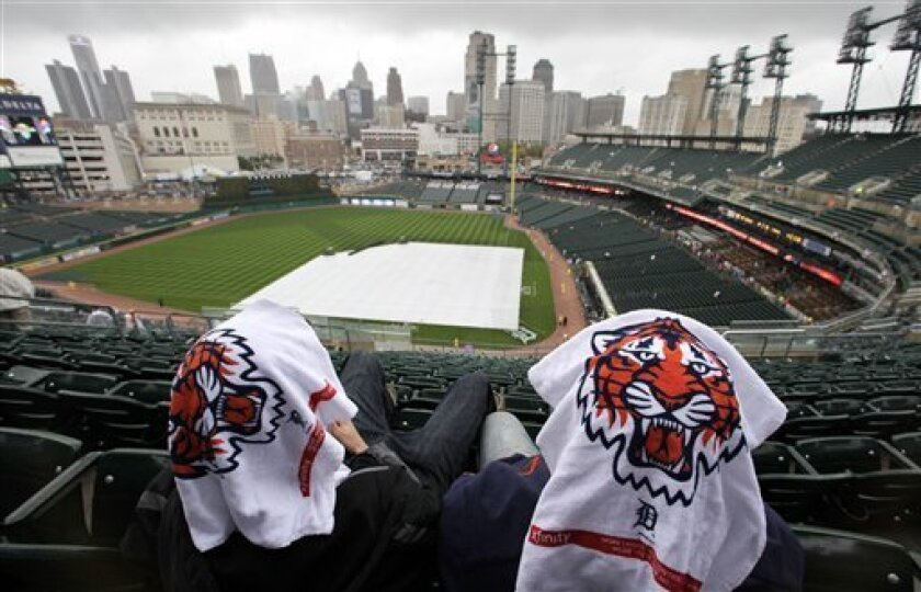 Two baseball fans with towels on their heads wait out the rain delay before Game 4 of baseball's American League championship series between the Detroit Tigers and the Texas Rangers, Wednesday, Oct. 12, 2011, in Detroit. (AP Photo/Charlie Riedel)