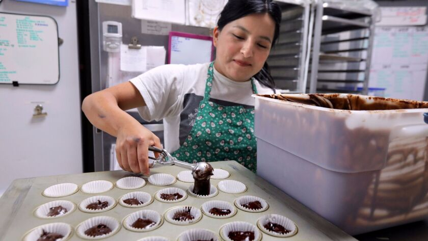 """In the kitchen at Little Cakes Cupcake Kitchen, head baker Jessica Sanchez pours chocolate for a special order of four dozen mini-sized """"Tuxedo"""" flavor cupcakes."""