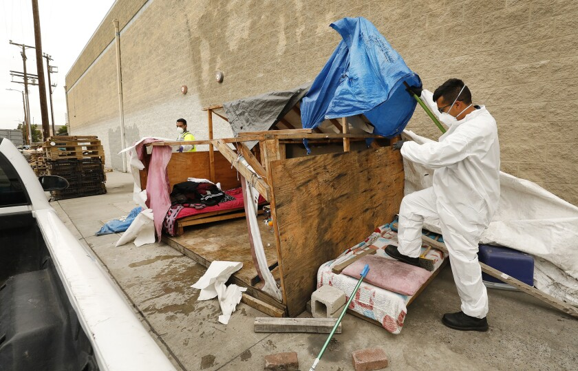 Jesus Sanchez, left, and Javier Villarreal of L.A.'s Bureau of Sanitation participate in the cleanup of a homeless encampment in May in South Los Angeles.
