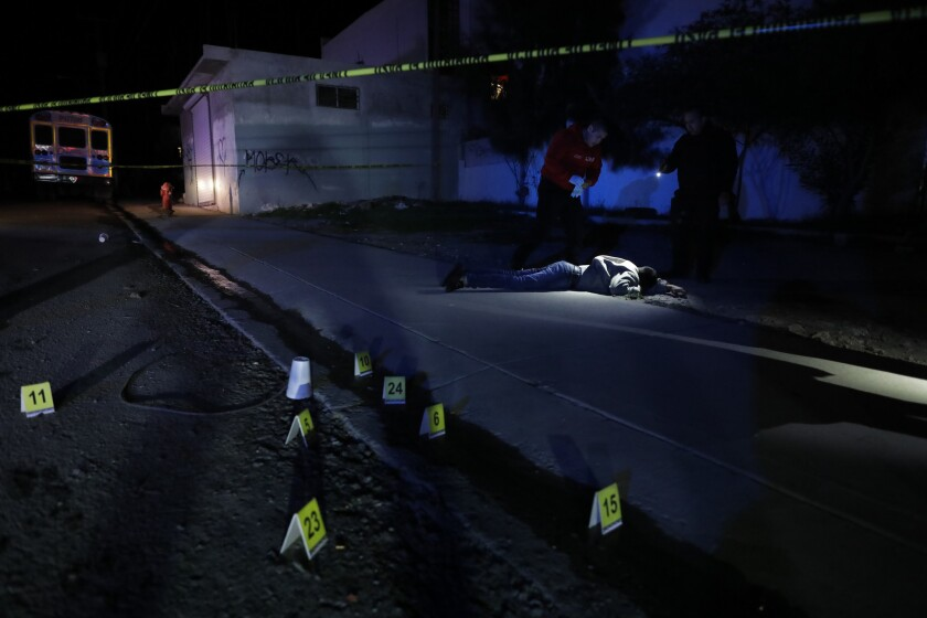 A paramedic and police officer look at the body of a man, estimated to be about 28, found with five gunshot wounds to his back and legs in Tijuana on Dec. 30, 2018.