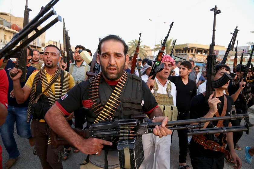 Iraqi Shiite tribal fighters deploy with their weapons while chanting slogans against the Islamic State of Iraq and Syria, or ISIS.