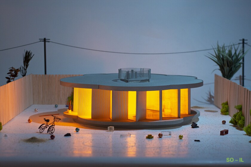 A photograph of a model shows a rounded structure with a saw tooth facade illuminated from within.
