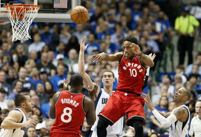 Toronto Raptors guard DeMar DeRozan (10) passes the ball over Bismack Biyombo (8) of the Democratic Republic of Congo as Dallas Mavericks' J.J. Barea of Puerto Rico, left, Dwight Powell, rear, and Devin Harris, right, watch in the second half of an NBA basketball game Tuesday, Nov. 3, 2015, in Dall