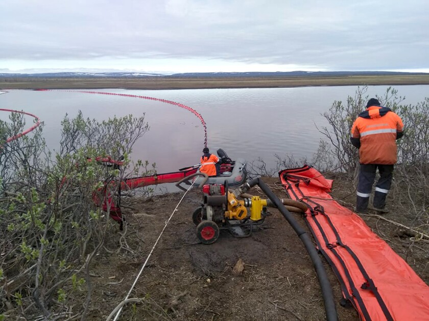 In this handout photo provided by the Russian Marine Rescue Service, rescuers work to prevent the spread of an oil spill outside Norilsk, 2,900 kilometers (1,800 miles) northeast of Moscow, Russia, on Tuesday, June 2, 2020. Russian President Vladimir Putin has declared a state of emergency in a region of Siberia after an estimated 20,000 tons of diesel fuel spilled from a power plant storage facility and fouled waterways.(Russian Marine Rescue Service via AP)