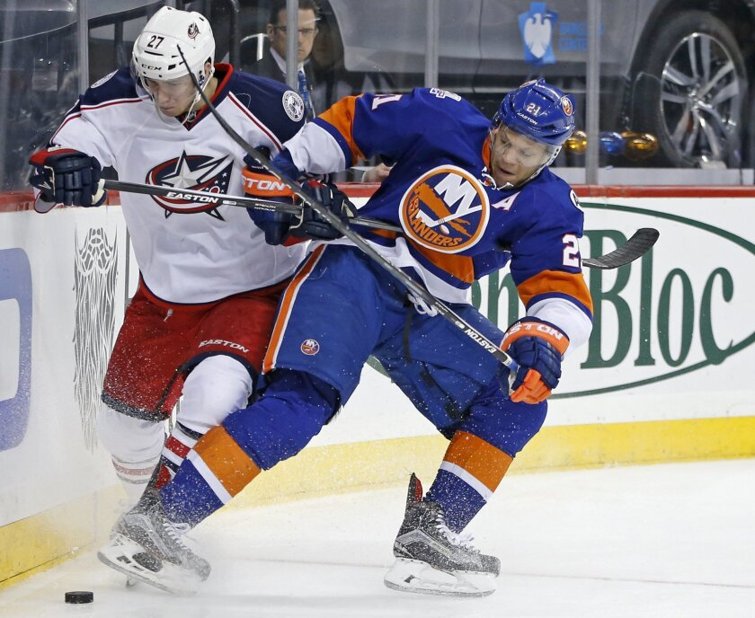 FILE - In this March 31, 2016, file photo, New York Islanders right wing Kyle Okposo (21) battles along the boards for the puck against  Columbus Blue Jackets defenseman Ryan Murray (27)during the second period of an NHL hockey game in New York. The Buffalo Sabres have signed Okposo to a $42 millio