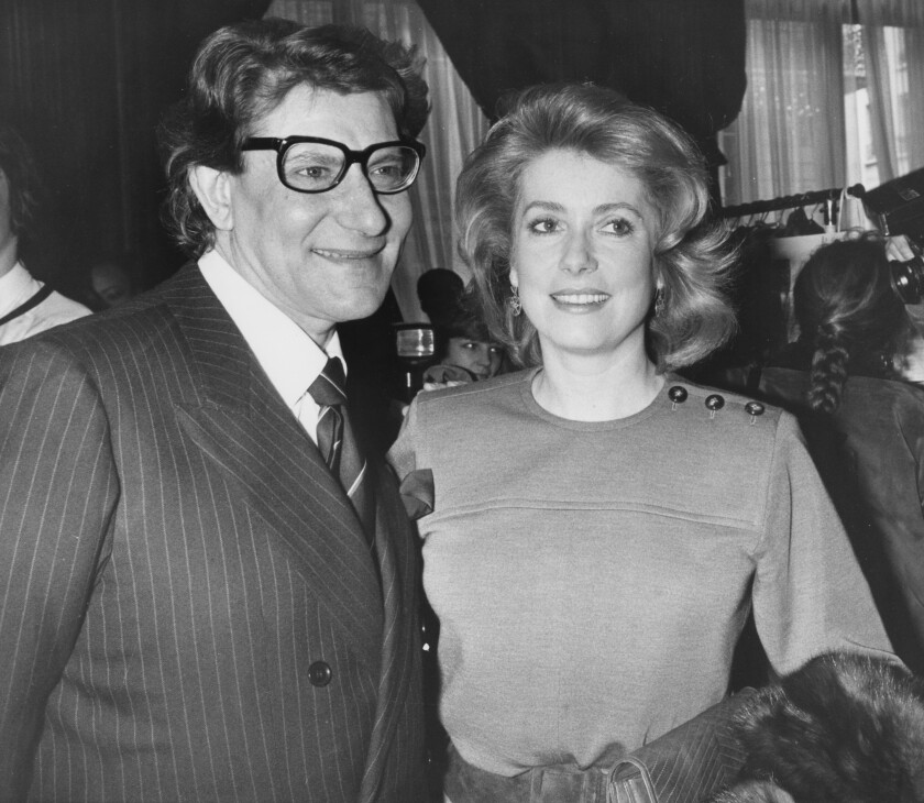 """FILE - In this Jan. 30 1985 file photo, French actress Catherine Deneuve congratulates French fashion designer Yves Saint Laurent after the presentation of spring-summer haute couture collection in Paris. Denueve's family said in a statement released Wednesday Nov. 6, 2019, that the 76-year-old actress suffered a """"very limited and therefore reversible"""" stroke. (AP Photo/Alexis Duclos, File)"""