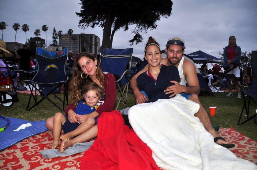 Yaimalis Fernandez, 3-year-old Jack Peck, and Corry and Lathena Pippen stay warm as they await the fireworks show at Scripps Park in La Jolla Cove.