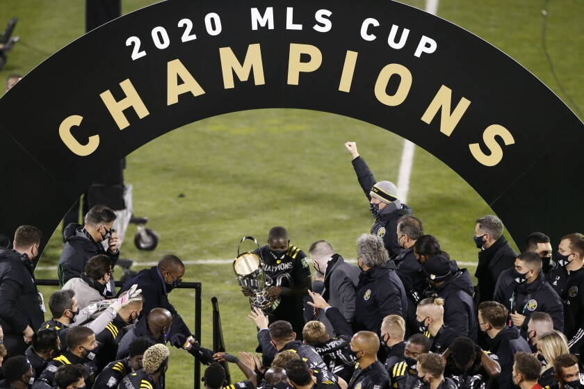 Columbus Crew's Jonathan Mensah, center, carries the trophy on stage after the Crew defeated the Seattle Sounders 3-0 in the MLS Cup championship game Saturday, Dec. 12, 2020, in Columbus, Ohio. (AP Photo/Jay LaPrete)