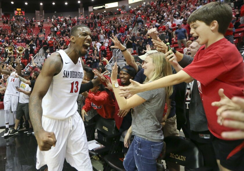 San Diego State's Winston Shepard, left, celebrates with fans after their 78-71 overtime victory over New Mexico in an NCAA college basketball game, Saturday, Feb. 6, 2016, in San Diego. (AP Photo/Lenny Ignelzi)