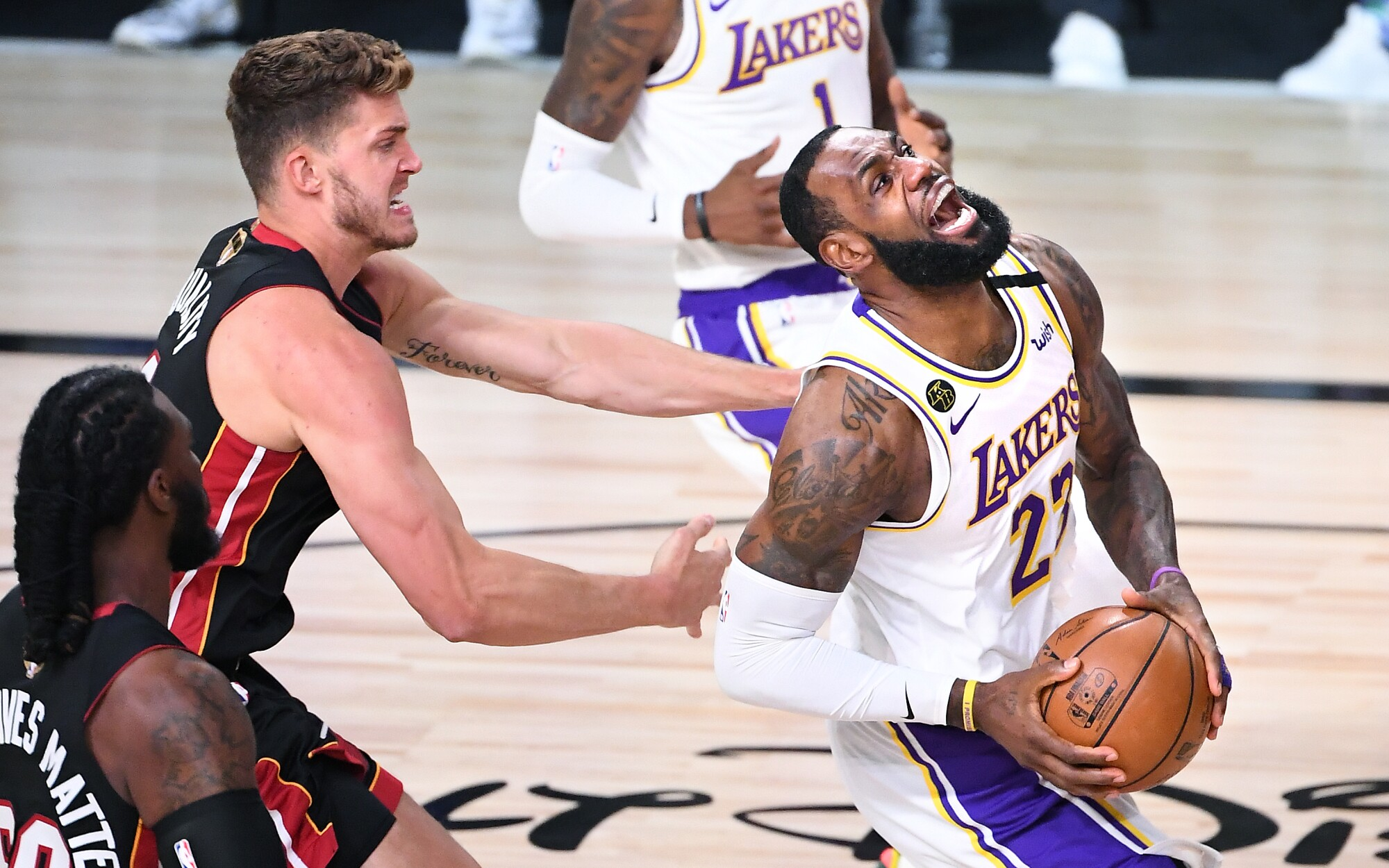 Lakers forward LeBron James is fouled on a drive by Heat center Meyers Leonard during Game 3.