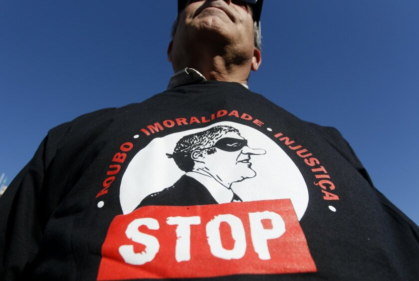 In this photo taken on Saturday, March 19, 2011, a man wears a shirt with a picture of portraying former Portugal's Prime Minister Jose Socrates in a robber's mask during a demonstration by public workers, in Lisbon. With Iberia still reeling from the aftershocks of Europe's debt crisis, economics