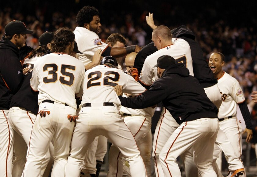 Nate Schierholtz (center, shaved head) is mobbed by teammates after hitting a game-winning home run in the Giants' 6-5 triiumph over the Padres.