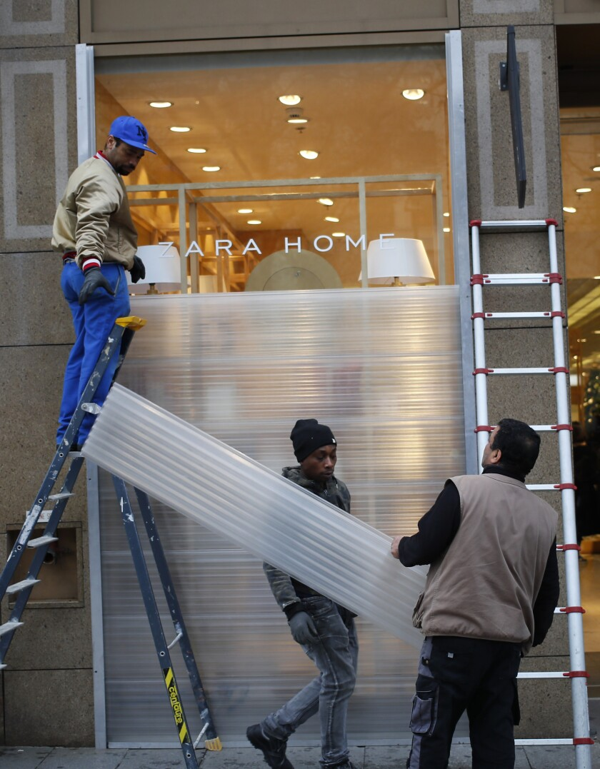 Workers set up protection on shop windows on the Champs-Elysees avenue, Friday, Dec. 7, 2018 in Pari