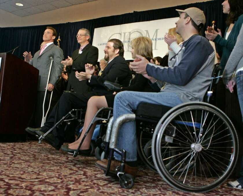 A technique that has been successful in managing Parkinson's disease symptoms could prove useful in helping some people with spinal cord injuries walk again. In this 2007 photo, then-Gov. Arnold Schwarzenegger is flanked by Californians with spinal cord injuries at an event for the California Institute for Regenerative Medicine.